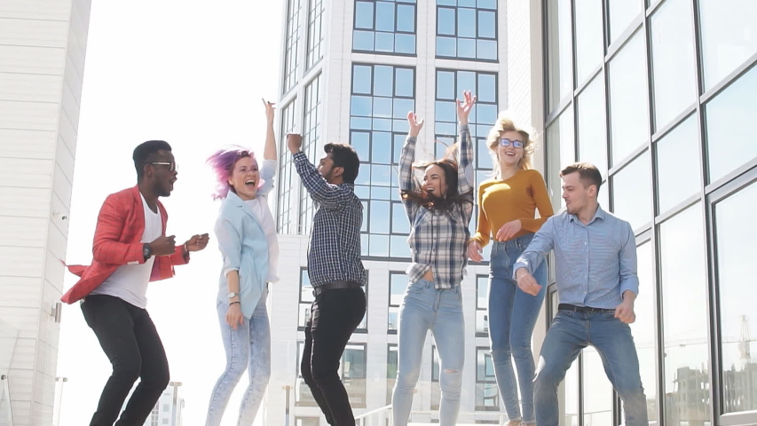 Multi-racial group of young businessmen celebrate a successful deal by dancing and jumping on the roof. | Shutterstock HD Video #1033097960