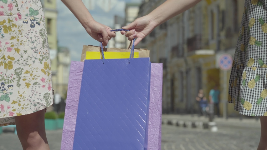 Close-up hands of fashionable girls holding shopping bags and pulling them to their sides on the street. Shopping concept. Fashionistas are fighting for purchases. | Shutterstock HD Video #1033108010