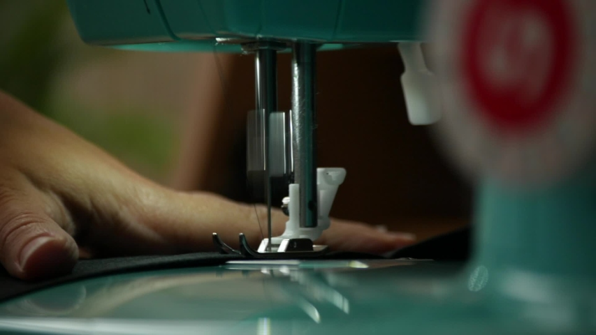 A female hand pushes material through a sewing machine
