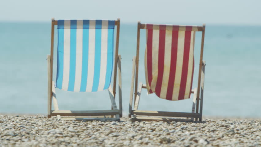 4K Deck chairs on a pebble beach as a boat rides by in the sea in slow motion, shot on RED EPIC