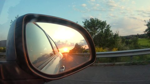Sunset view in side mirror of car.