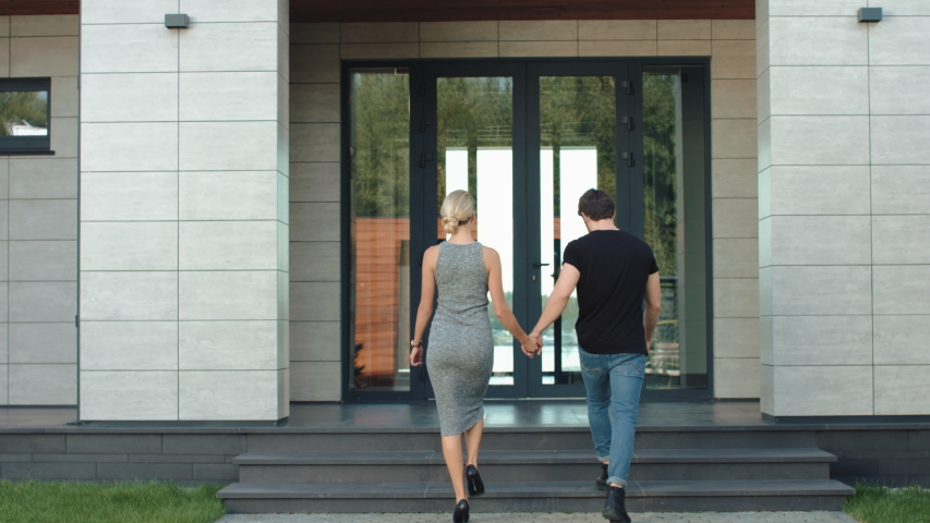Beautiful couple entering modern villa back view. Rich couple holding hands near private house. Cheerful man and woman going up stairs in modern building. Happy family going inside luxury house.