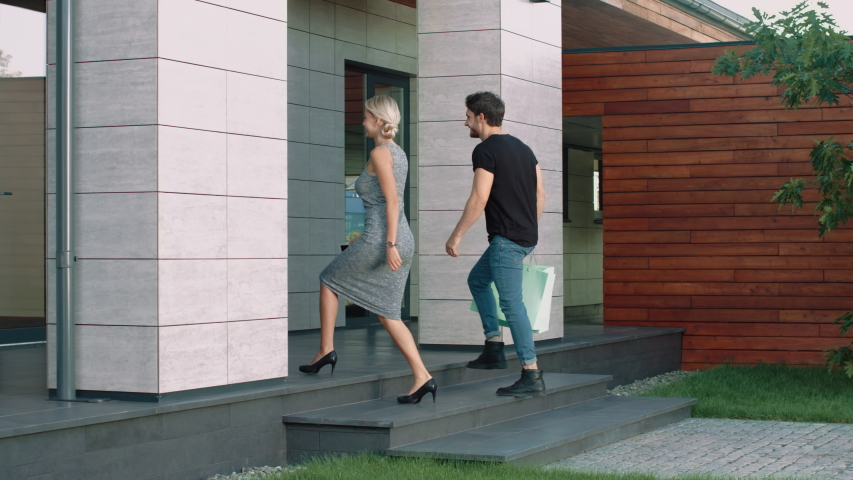 Modern couple entering business center. Luxury woman and man going up stairs at building. Cute couple coming rich home after shopping. Fashion family going up stairs at luxury apartments with bags