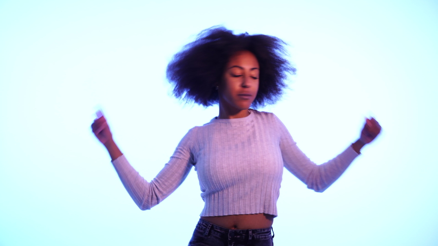 Video of Inspired cool African American woman dancing feeling the music and enjoying life on blue moody neon disco light background. In People, Music festival, Youth Party night lifestyle.  | Shutterstock HD Video #1033219220