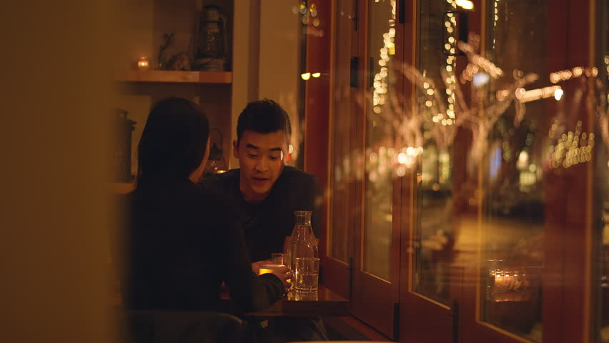 A young couple talking on a romantic dinner date, through the window