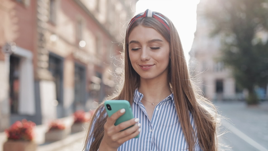 Smiling young woman wearing in blue and white striped dress shirt walking around old street using smartphone. Communication, social networks, online shopping concept. | Shutterstock HD Video #1033262030