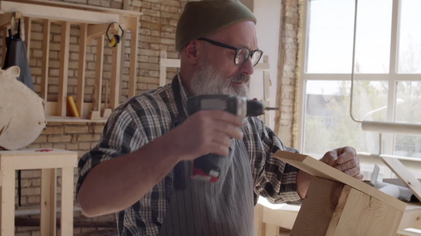 Medium shot of carpenter with beard and spectacles standing at workbench and screwing screw in roof of wooden bird box using electrical screwdriver | Shutterstock HD Video #1033263500