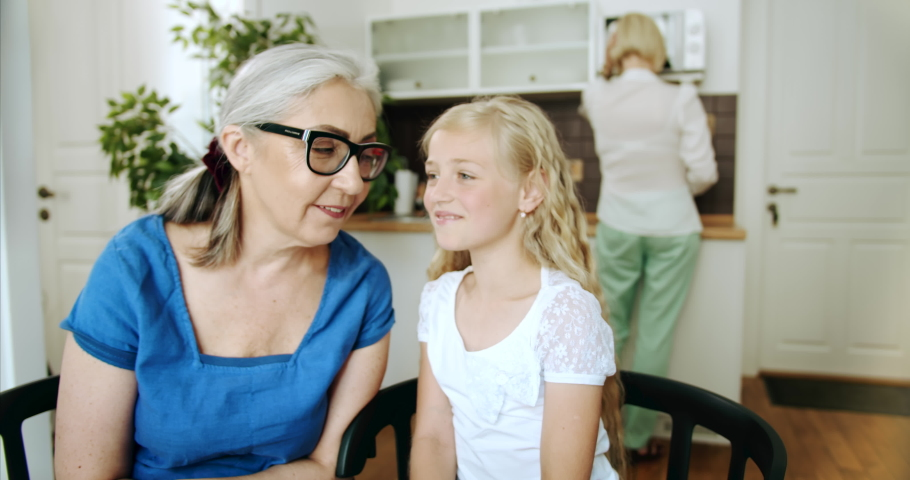 Cute blond girl in white blouse whispering secret to granny's eay, family spending time together indoors | Shutterstock HD Video #1033267760