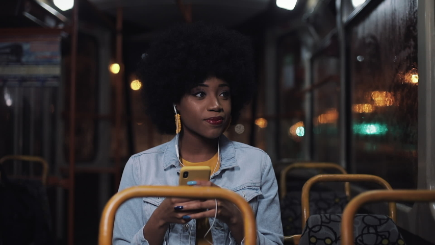 Attractive young african american woman using smartphone riding at public transport and looking out the window. Night time. City lights background.