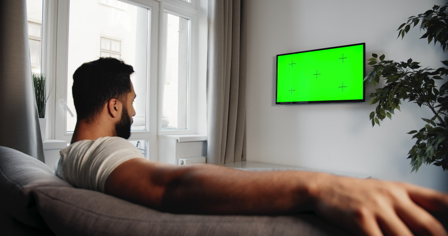 Male turning on prekeyed tv with remote control, sitting on sofa indoors, advertisement template, sideview | Shutterstock HD Video #1033278890