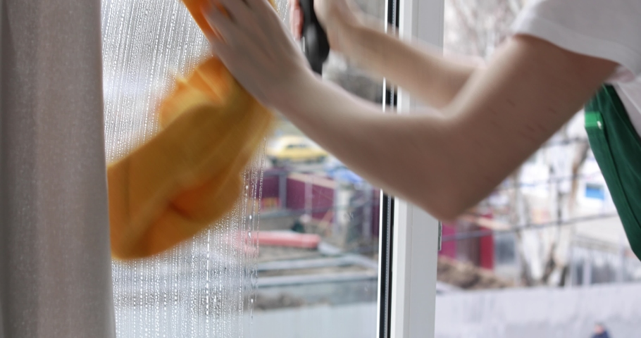 Woman cleaning window with squeegee and detergent indoors  | Shutterstock HD Video #1033300970