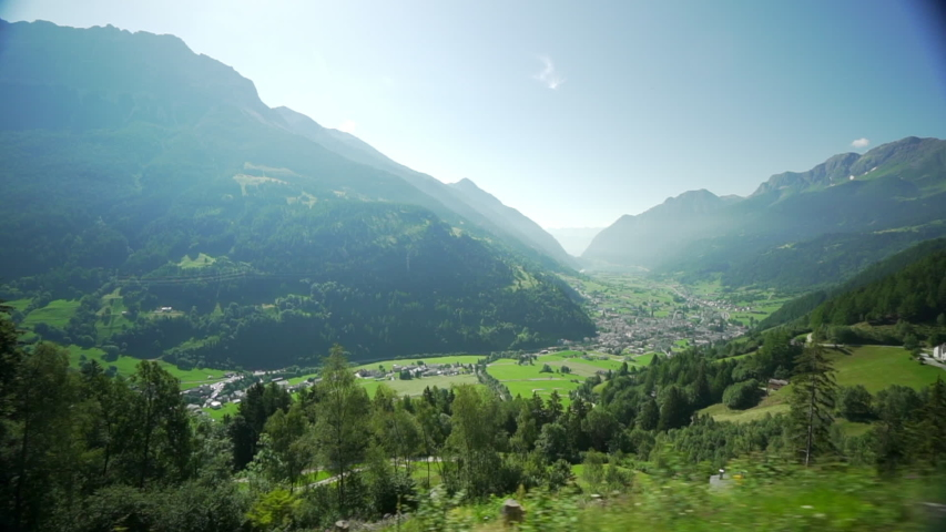 Pan Left to Right: Valley Surrounded by Nature Filled Mountains in Val Poschiavo | Shutterstock HD Video #1033302020