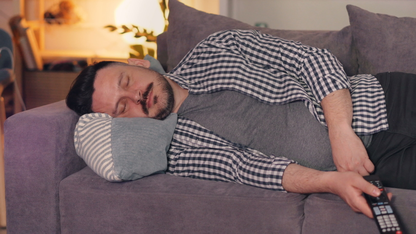 Portrait of middle-aged guy in casual chothes sleeping on couch at home holding TV remote control lying relaxing. People, apartment and lifestyle concept. | Shutterstock HD Video #1033306310