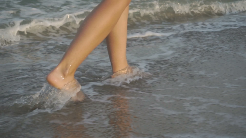 Track shot on the woman's legs while walking in the beach | Shutterstock HD Video #1033375190