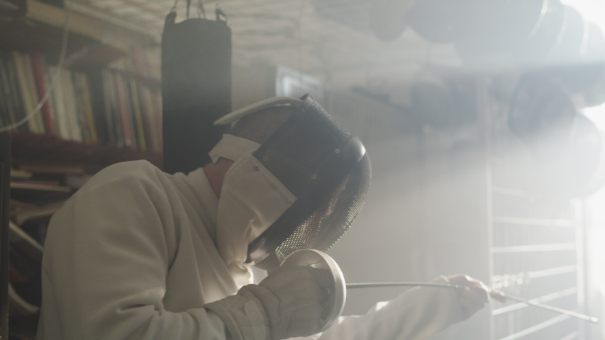 A man in fencing gear checks his foil in a foggy equipment room   Shutterstock HD Video #1033579820