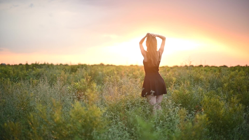 Cheerful young woman in white dress walking through beautiful lavender filed at golden sunset in summer | Shutterstock HD Video #1033900460