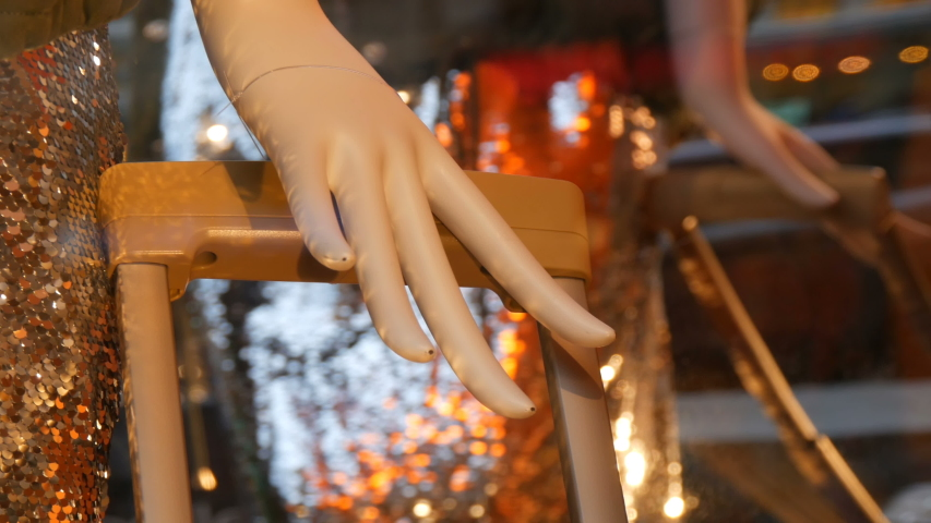 Part of a woman's mannequin hand and suitcase handle. Dummy in the shop window. Beautiful, expensive, fashionable clothes are shown on a boutique showcase | Shutterstock HD Video #1033944110
