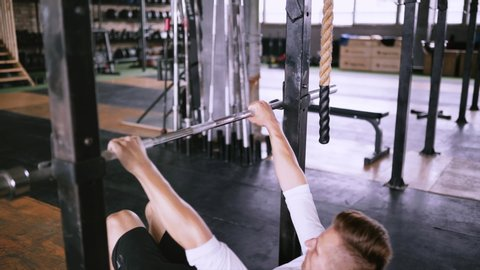 Close-up view  man in white t-shirt pulls up on bar in gym and wears lift  and grip gear  efficient incline pull-ups to be fit  best exercises in the  gym  strengthening muscles of back chest