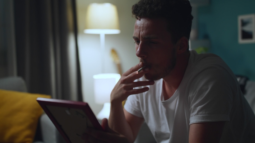 Sad man looking at photo of ex-girlfriend, and smoke | Shutterstock HD Video #1033982000
