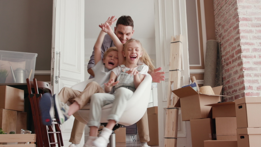 Active Family Group Move in Rent Real Estate. Positive Looking at Relocating or Unpacking of Carton Pack by Playful Dad. Two Caucasian Babies Ride a Chair. Enjoying Life or Dream of Small Child by Day | Shutterstock HD Video #1034046740