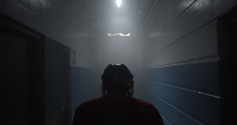 Dramatic over the shoulder of hockey player walking down hockey arena hallway towards ice rink getting ready to play. | Shutterstock HD Video #1034197010