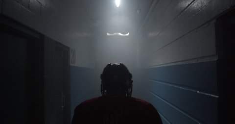 Dramatic over the shoulder of hockey player walking down hockey arena hallway towards ice rink getting ready to play.
