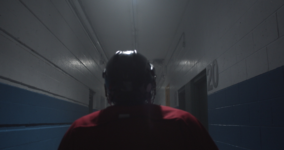 Over the shoulder silhouette of hockey player walking down arena corridor towards the ice. | Shutterstock HD Video #1034200310