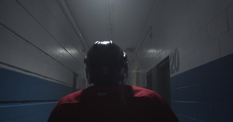 Over the shoulder silhouette of hockey player walking down arena corridor towards the ice.