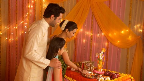 Nuclear Indian family offering flowers and bowing head in front of Hindu God. 4K stock footage of a nuclear Indian family worshiping together on the occasion of Janamashtmi - Lord Krishna Birthday