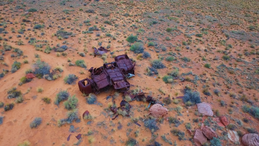 Slowly ascending / panning down aerial shot of 3 rusty cars in the desert | Shutterstock HD Video #1034264600
