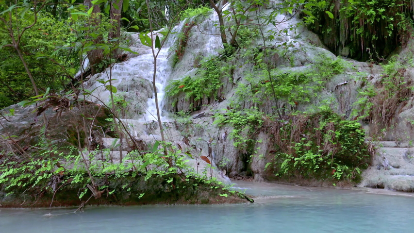 Fantastic panoramic view of Erawan cascade waterfall. Kanchanaburi National Park, Thailand. Branches of tropical exotic plants, foliage. Lush vegetation. Beautiful ecology. Wild forest environment