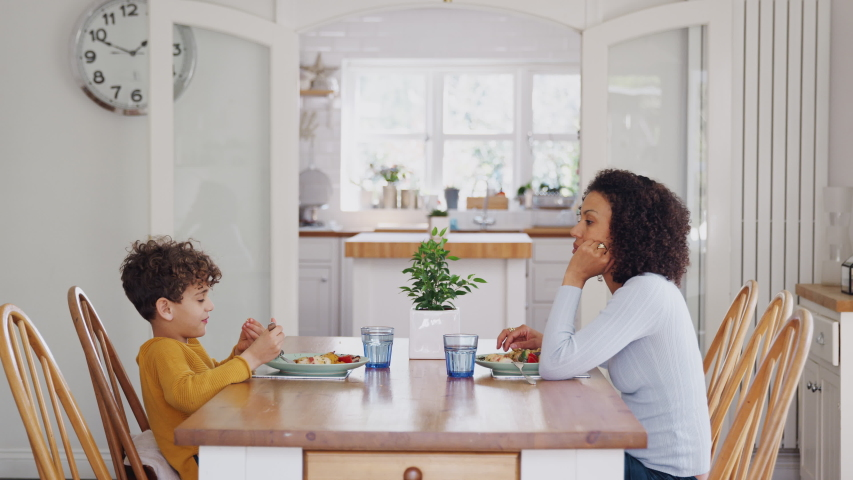 Single Mother Sitting At Table Eating Meal With Son In Kitchen At Home | Shutterstock HD Video #1034298890