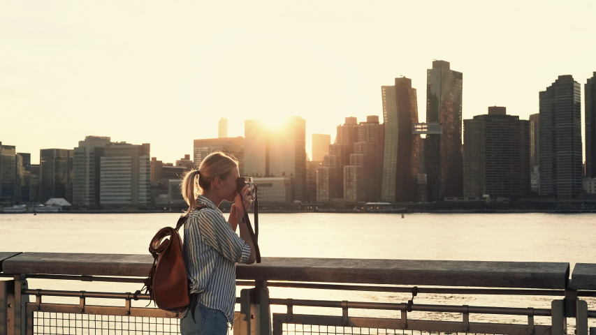 Hipster girl photographing scenic landmark of Manhattan island via film instant camera looking at made image and clicking photo with smartphone application for sharing to travel website | Shutterstock HD Video #1034314070