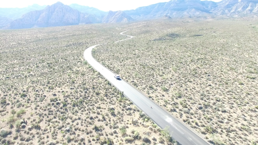 Aerial drone following a vehicle in the Nevada desert with mountains in the background. | Shutterstock HD Video #1034390570