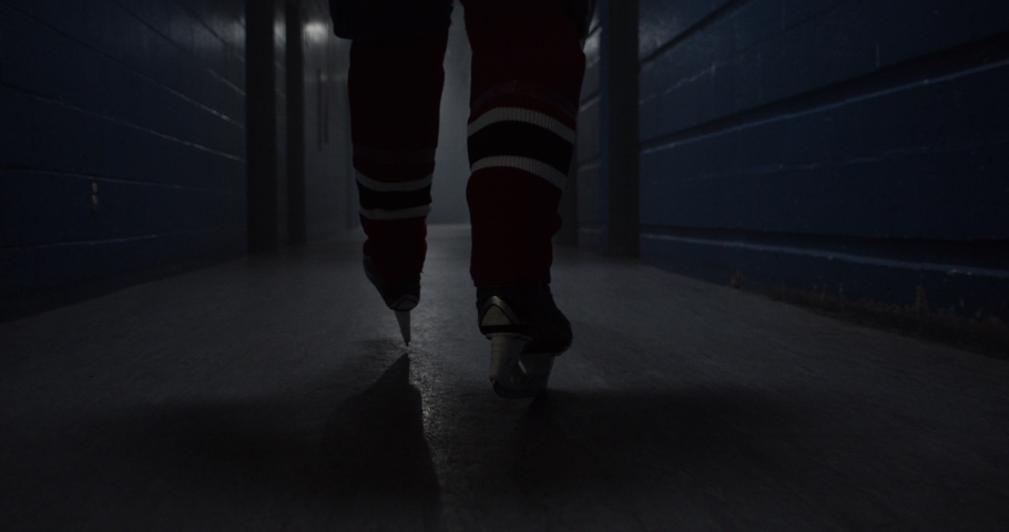 A hockey player walks down a hallway with intensity towards hockey arena featuring his hockey skates, building drama. | Shutterstock HD Video #1034396600