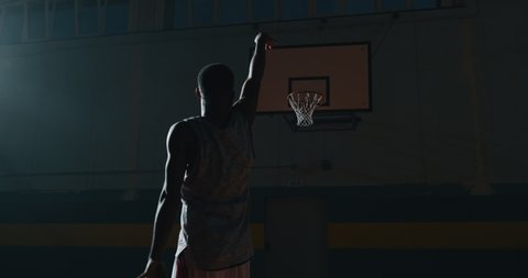 Cinematic slow motion shot of an young professional african male player is making a  slam dunk during a basketball work out in a gym.
