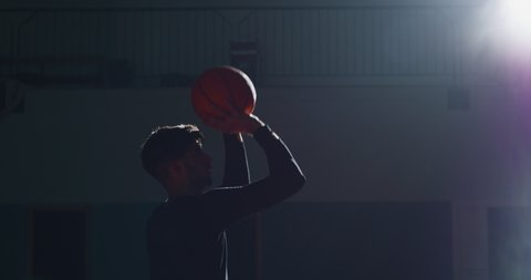 Cinematic slow motion shot of an young professional male player is making a  slam dunk during a basketball work out in a gym.