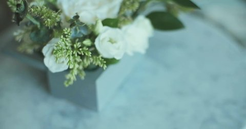 Beautiful floral arrangement with white roses on the background of the bride in a dress