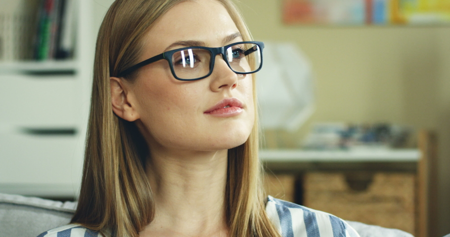 Close up of the young happy pretty Caucasian woman in glasses turning her face, smiling to the camera while sitting on the couch in the living room. Portrait. | Shutterstock HD Video #1034506820