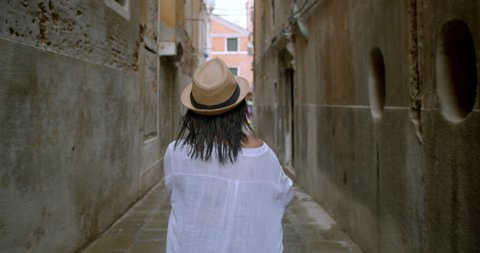 Attractive young traveller wearing fedora runs through a small street in Venice Italy happy to be going on an adventure