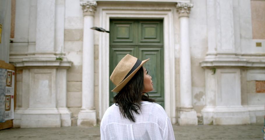 Woman traveller in front of massive antique door from behind in fedora in historic Venice Italy | Shutterstock HD Video #1034515280