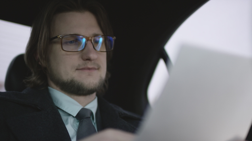 Handsome man with brown hair in pistachio shirt and grey coat and galsses riding in car and check documents with pen | Shutterstock HD Video #1034569400