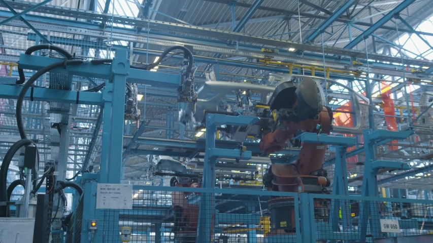 Car production industry. Automotive plant. Robots at the assembly line | Shutterstock HD Video #1034668880