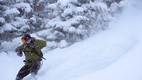 Slow motion skier carving through thick fresh powder snow. Skier on the mountain. Fresh powder snow. winter sport. Ski carving in the snow. Free ride ski. Backcountry skier on the mountains