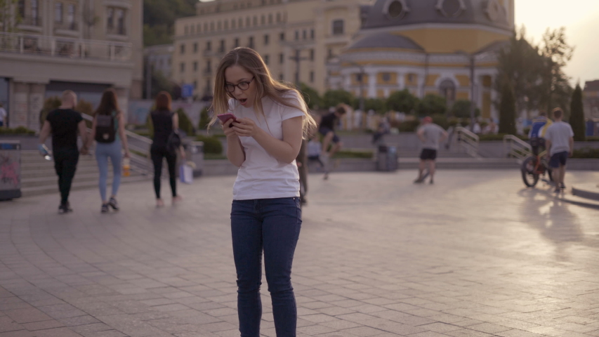 A lucky young girl looks at the phone and sees the message good news on the phone. Woman rejoices and laughs, jumps. 4K | Shutterstock HD Video #1034742920
