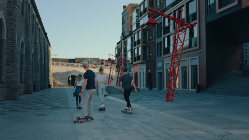 Group of Girls and Guys Riding on Skateboards Through Fashionable Hipster District. Beautiful Young People Skateboarding Through Modern City Street. Following Slow Motion Camera Shot | Shutterstock HD Video #1034749190