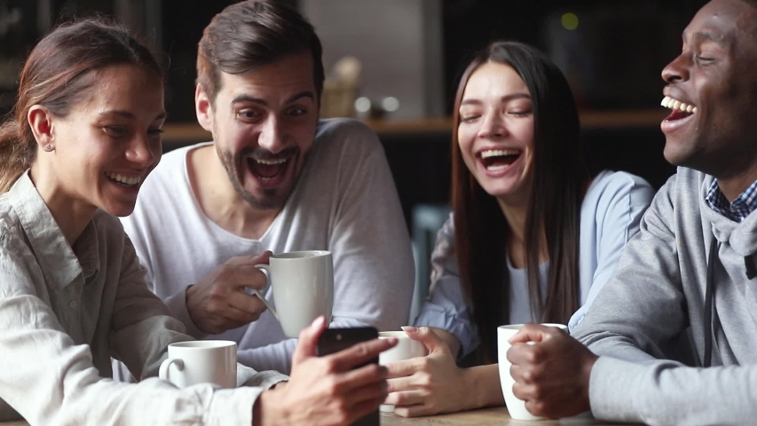 Different ethnicity colleagues spend free time lunch together gathered in cafe drink coffee laughing feels overjoyed, girl showing to friends funny video hold cellphone having fun online prank concept