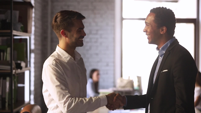 European and black businessmen stands in co-working office discuss document contract details finish talk shaking hands, client and executive manager effective meeting, synergy working together concept