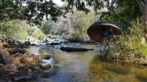 Hogenakkal , Tamilnadu / India - 12 22 2018: Hogenakkal, Tamilnadu, India - 22-Dec-2018: A man crossing a river stream of the Cauvery river carrying a coracle and a paddle in Hogenakkal, Tamilnadu, In