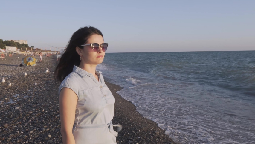 Girl on the beach looking at the sea and big waves | Shutterstock HD Video #1034873540